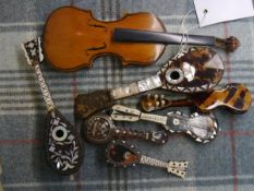 A group of six miniature tortoiseshell string instruments including lutes and guitars, some inset
