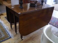 A George III mahogany gateleg dining table, c. 1800, the rectangular top with D-end flaps, raised on