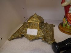 A late 19th century brass desk inkwell, cast with masks, scrolls and foliage and with pottery liner.