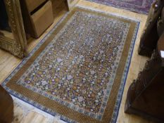 An Indo-Persian rug, ochre and cream foliate design on a blue field, within geometric borders;