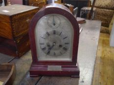 A 1920's mahogany cased mantel clock, of arched form, the silvered dial with Roman numerals and