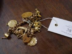 A 9ct gold curblink charm bracelet, suspending various charms including a South African 1 pond coin.