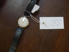A vintage Omega gentleman's yellow metal wristwatch, with baton numerals, automatic movement, on a