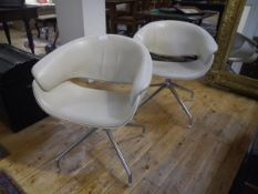 """A pair of B&B Italia """"Sina"""" armchairs, each swivelling chair upholstered in cream leather on a steel"""