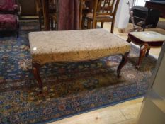 A Louis XV style low stool, the upholstered seat over a scroll carved seat rail, raised on