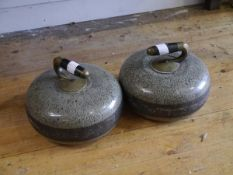 A pair of granite curling stones, each with ebonised wood and brass handle. Diameter 26cm