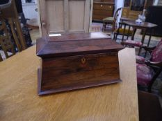 A large early 19th century rosewood twin compartment tea caddy, of sarcophagus form, the fitted