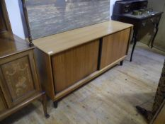 A Gordon Russell sideboard, c. 1960, the rectangular top above two sliding doors with integral
