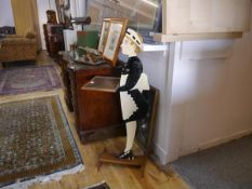 A 1930's painted wooden dumbwaiter table, modelled as a maid in cap and apron, holding an oak
