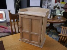 A small pine hanging cabinet, with galleried top, panelled door and fitted interior. 45cm by 33cm by