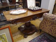 A 19th century centre table, the rectangular top with rounded corners above a scroll and flower-