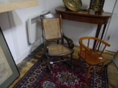 A 19th century child's walnut-framed rocking chair, with canework seat and back and downscrolled