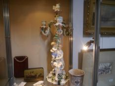 A German porcelain four light candelabrum, 19th century, the figural base modelled as a mother and