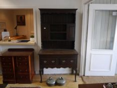 A George III oak dresser base with later associated rack, the rack with an arrangement of shelves