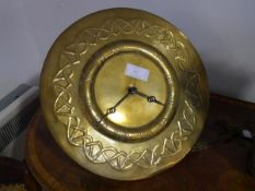 An Art Nouveau brass wall clock, c. 1910,the dial repousse with Roman numerals within a Celtic band,