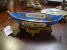 A French 19th century porcelain twin-handled dish of navette form, with gilt-metal ring handles on a