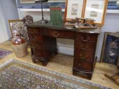 A George III style leather-inset mahogany pedestal desk, 20th century, of serpentine form, raised on