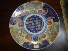 A Japanese porcelain charger, Meiji period, painted in enamels with birds amidst landscapes and