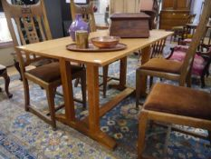 A golden oak refectory table in the Arts and Crafts taste, the rectangular top on paired chamfered