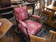 An Edwardian inlaid armchair, the crest rail with foliate inlay above a stuffed over seat flanked by