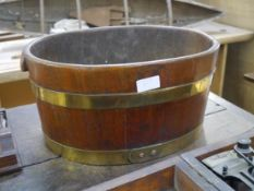 A small brass-bound coopered barrel, c. 1900, of oval form, carved with twin handles, possibly a