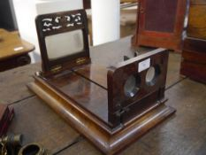A late 19th century walnut stereoscopic viewer, with rectangular waisted platform,carved with a