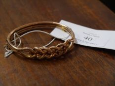 A 9ct gold bangle, chased and cast with entwined scrollwork, fitted with safety chain. 11 grams