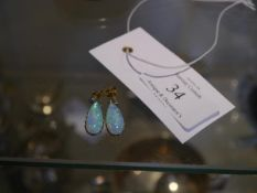 A pair of opal and diamond drop earrings, each claw set with a tear-drop opal beneath a collet-set
