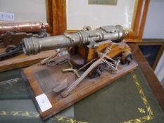 A bronze scale model cannon, on wooden carriage with ropes and loader, bearing plaque inscribed ""