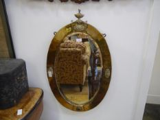 An Edwardian brass mirror, of oval form, with urn surmount and applied with a cabochon and pair of
