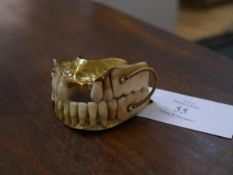 A full set of gold-mounted false teeth, 19th century, the top and bottom sets mounted in gold (