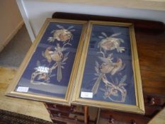 A pair of silk needlework panels, each depicting an exotic bird on a fruit laden bough, worked in