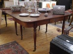 A George IV mahogany extending dining table, with rounded corners above a plain frieze, raised on