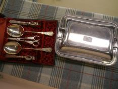 A late Victorian cased service of pair of nutcrackers, pair of serving spoons and grape scissors, in
