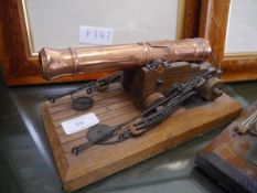 A scale model cannon, the metal with copper finish, mouned on a wooden carriage and stand. Length