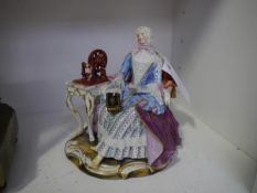 A late 19th century Meissen porcelain figure, a lady seated with bible in her right hand beside a
