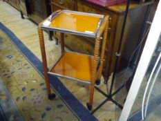 A 1950's wrapped metal orange two tier trolley with removable trays