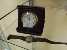 A 1920's leather-cased folding travel clock; together with a vintage white metal wristwatch
