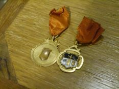 Two 9ct gold fobs or medals, one centred by an enamel crest and bearing the date 1938 to the