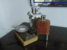 A group of barware comprising: white metal cocktail shaker; rattan and white metal hip flask;