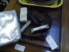 A group of harmonicas including Hohner and Blecanto and Harmonic gigging brace