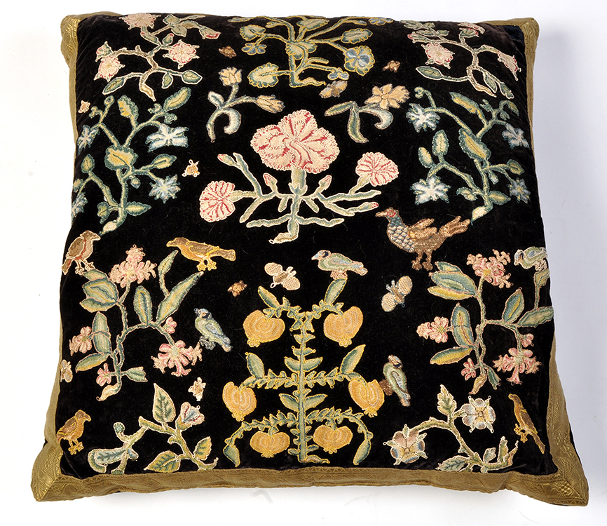 An antique needlework fragment cushion, decorated with flowers, bugs and birds,