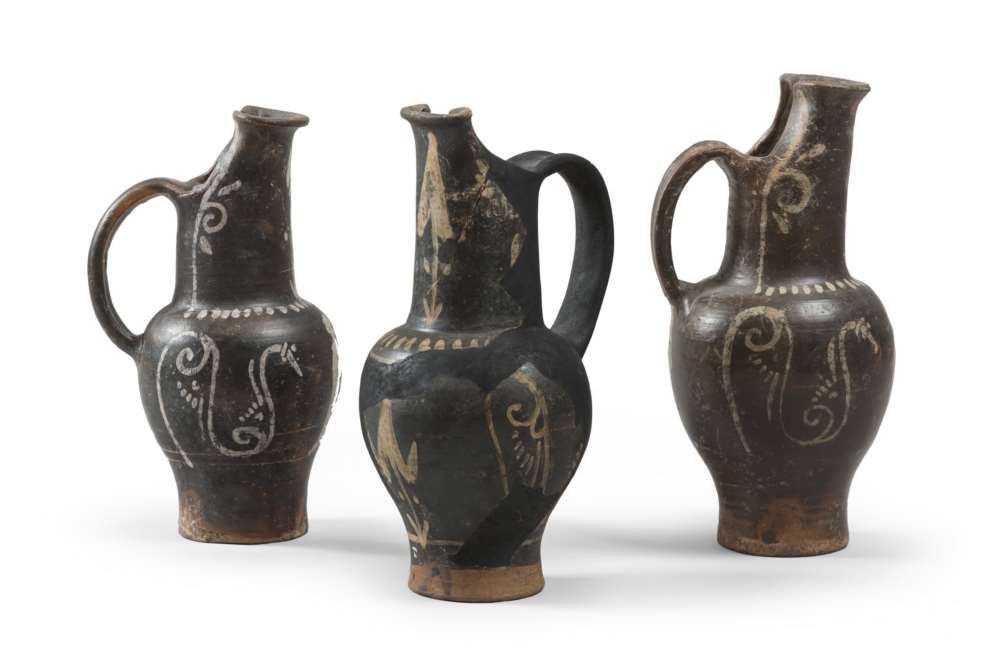 THREE ETRUSCAN OINOCHOAI OF THE GROUP OF THE GHOST, 4TH SECOLO B.C. in clay and opaque black