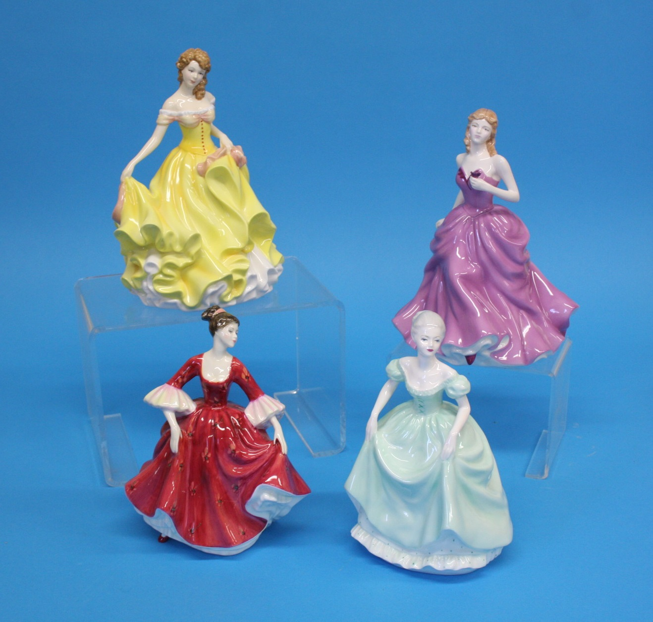 Three Royal Doulton figurines and a Coalport lady