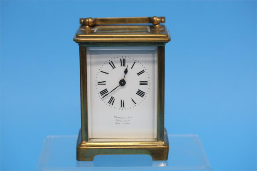 A small brass carriage clock with enamelled dial,