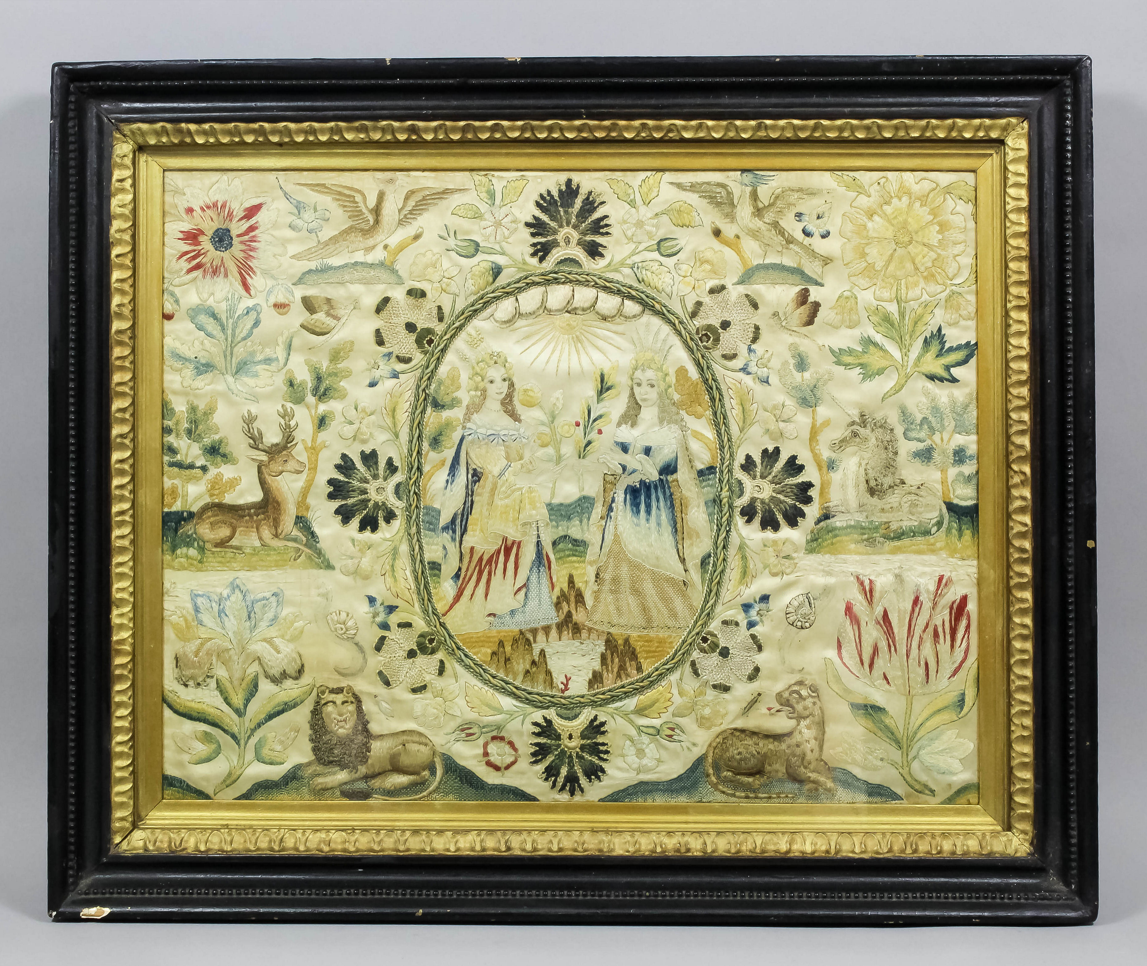 A mid 17th Century stumpwork picture depicting two ladies, in a central oval cartouche, surrounded