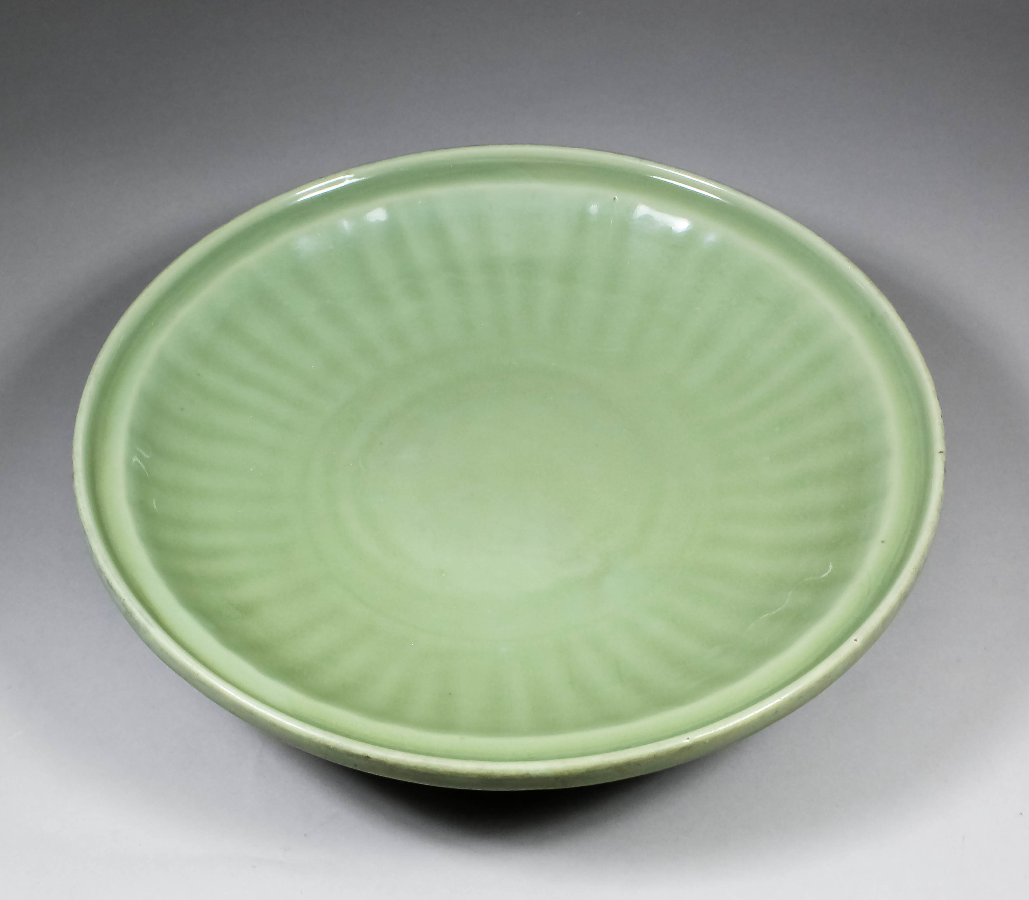 A Chinese Longquan celadon glazed circular charger with fluted border and moulded rim, 15.75ins (