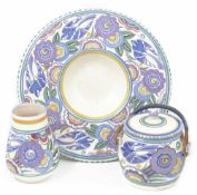 A small collection of 'Bluebird' Poole pattern comprising a small vase, biscuit barrel and charger