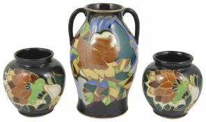 A large Gouda style twin handled vase decorated with stylised flowers and leaves against a black
