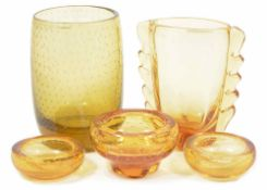 A collection of Whitefriars amber glassware comprising three ashtrays and two vases the largest vase
